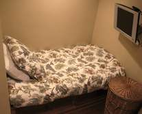 Den off of entryway with twin bed and flat screen TV