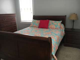 Bedroom #2 with queen size bed, chest of drawers and an en suite bathroom.