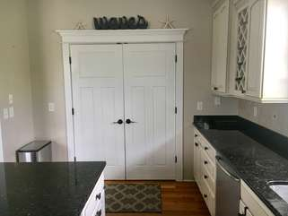 The double doors in the kitchen open to reveal the stacked washer and dryer.