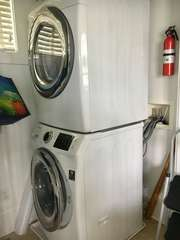 Stackable washer and dryer is in the kitchen.