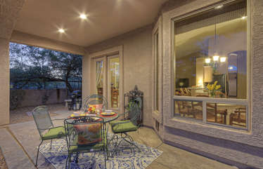 Lovely covered patio has comfy dining furniture for outdoor eating and viewing spectacular sunsets