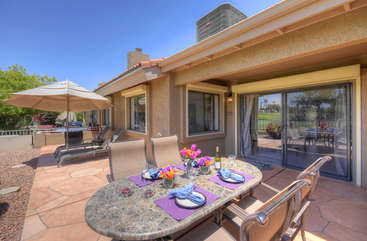 Large patio at back of home has places to dine and relax while admiring golf course view
