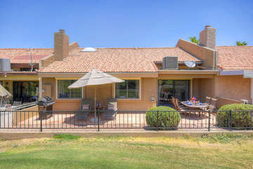 Patio with fairway views is one of home's many appreciable amenities guests will love