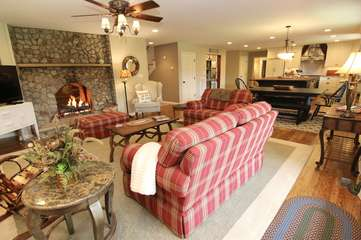 Family room with see-thru fireplace & glass doors leading to wrap around porch