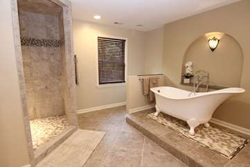 Master bathroom w/clawfoot tub, walk in shower, dual vanities, heated tile floor & walk in closet