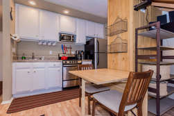 Kitchen equipped with stove, oven, refrigerator, and coffee maker and seating area.