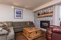 Living room with gas fireplace, flat screen TV, large section couch/sofa sleeper, and private outdoor patio