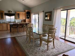 The main living area is open to the kitchen and dining areas. Sliding glass doors open to the deck on the front of the house.