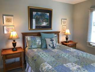 The first floor fourth bedroom has a queen bed, an HDTV and an en suite bathroom.
