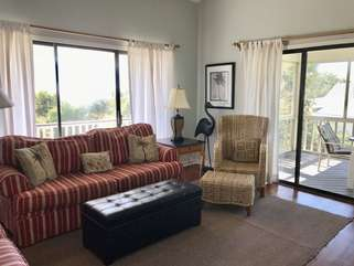 A comfortable living room with outside views and sliding doors to the screen porch.