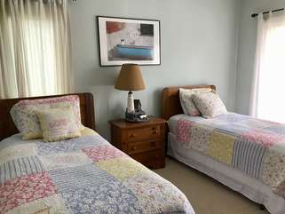 Across the hall is the second bedroom with twin beds and a sliding glass door that opens to the back deck.