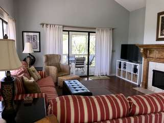 The living room has a large screen HDTV and plenty of seating.