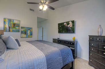 First floor master suite has king bed and television.