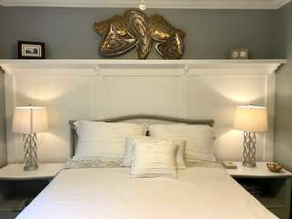 The guest bedroom has a queen size bed and beautiful white decorative woodwork.