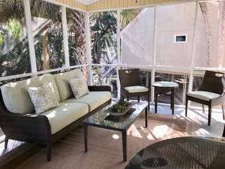 The screen porch is spacious with plenty of seating.