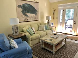 The living room is nicely appointed with comfortable furnishings. The doors open to the screen porch