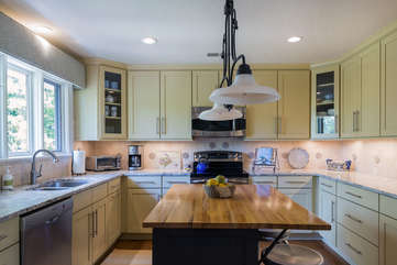 The kitchen has stainless steel appliances, granite counter tops and a wood topped island.
